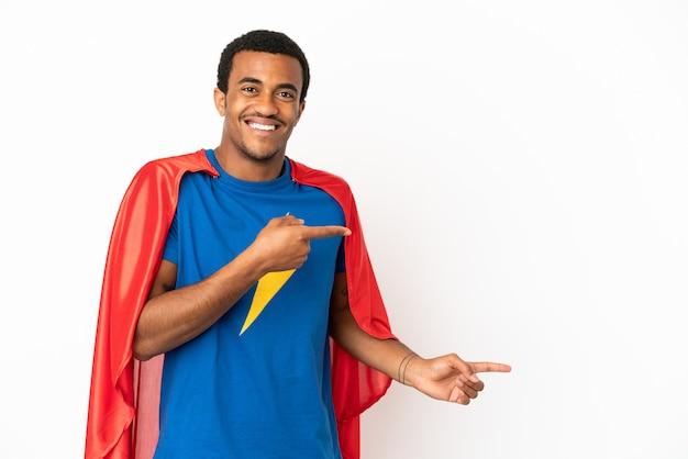 African american super hero man sur fond blanc isolé surpris et pointant vers le côté