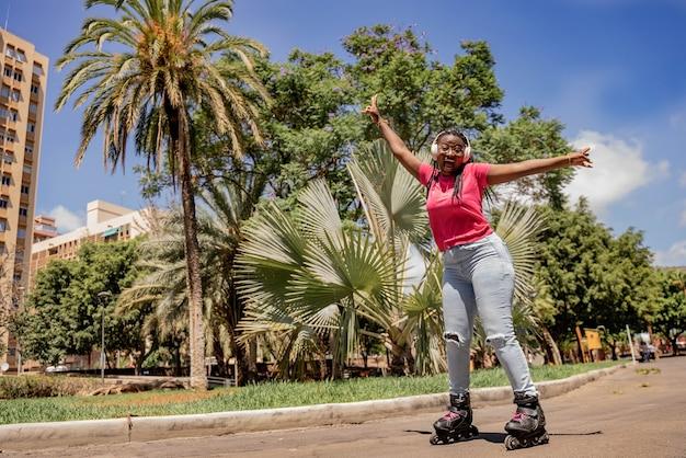 African american teen s'amuser en faisant du roller dans le parc