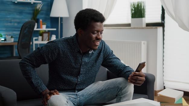Un afro-américain en appel vidéo en ligne à l'aide d'un téléphone dans un salon lumineux, un internaute en ligne travaillant à domicile, une connexion avec le monde pour la communication de bureau et la planification de projet