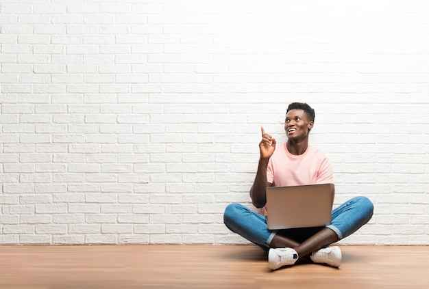 Afro-américain assis sur le sol avec son ordinateur portable pointant avec l'index une excellente idée