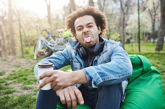 Afro-américain attrayant ludique avec coiffure afro qui sort la langue et être enfantin alors qu'il était assis sur une mauvaise chaise de haricots avec une tasse de café