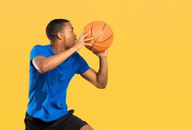 Afro-américain basketteur homme sur mur jaune isolé