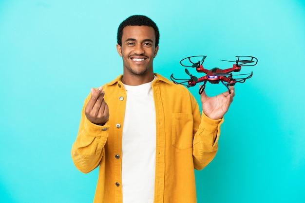 Afro-américain bel homme tenant un drone sur fond bleu isolé faisant un geste d'argent