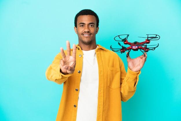 Afro-américain bel homme tenant un drone sur fond bleu isolé heureux et comptant trois avec les doigts
