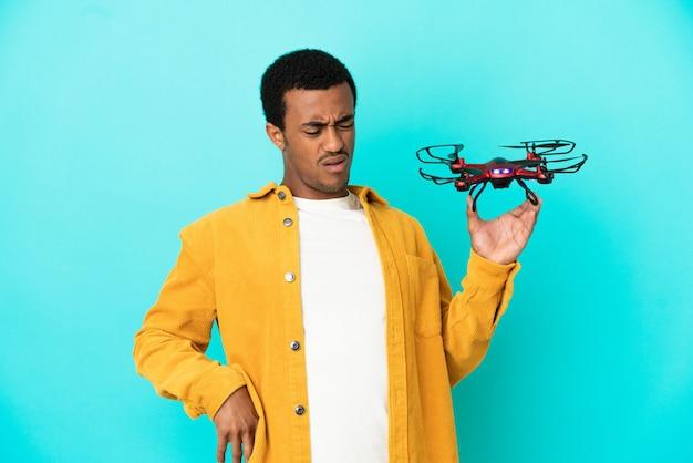 Afro-américain bel homme tenant un drone sur fond bleu isolé souffrant de maux de dos pour avoir fait un effort