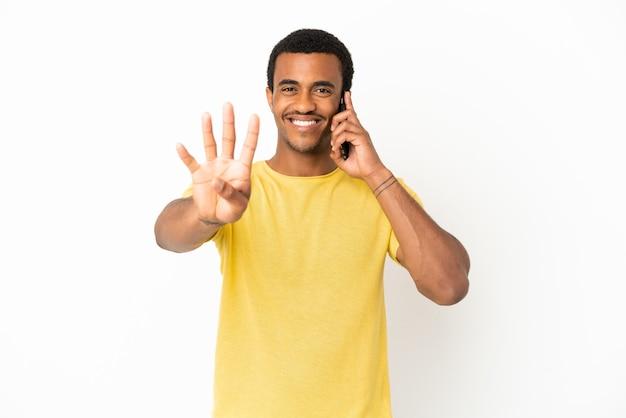 Afro-américain bel homme utilisant un téléphone portable sur fond blanc isolé heureux et comptant quatre avec les doigts