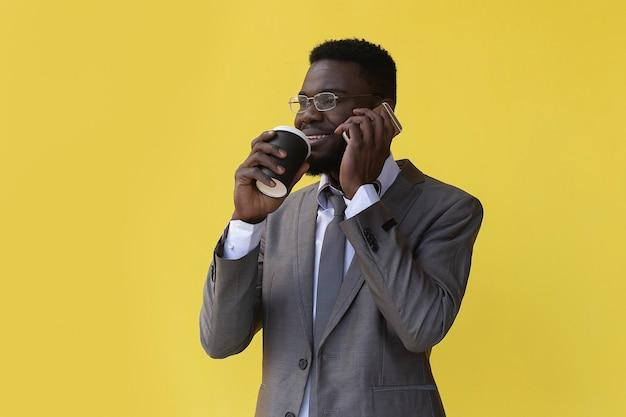 Afro-américain boit du café et parle au téléphone, sur fond jaune