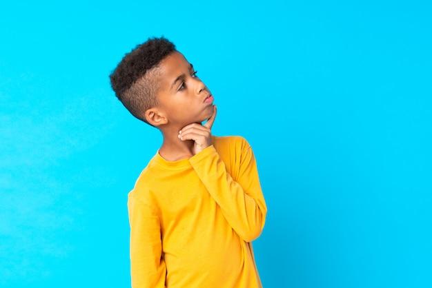 Afro-américain de boyblue ayant des doutes et avec une expression du visage confuse