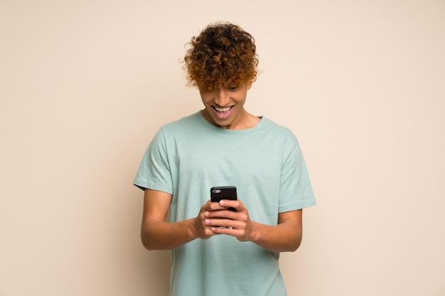 Afro-américain avec une chemise verte surpris et envoyant un message