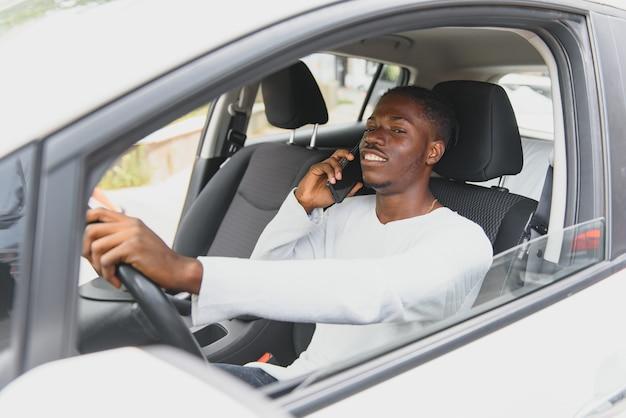 Afro-américain conduisant une voiture électrique.