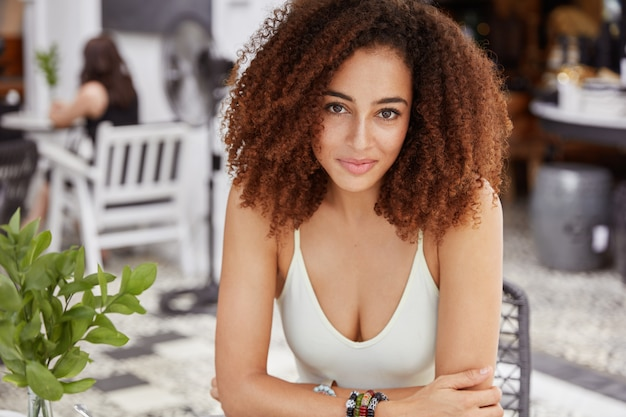 Afro-américain confiant avec une coiffure touffue, a une peau saine, s'assoit dans un café, rencontre un collègue, parle, attend l'ordre.