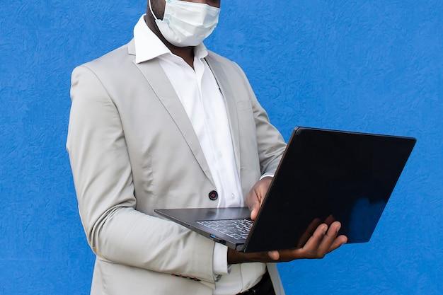 Afro-américain dans un masque de protection avec un ordinateur portable à la main