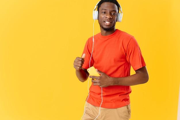 Afro-américain avec des écouteurs écoutant le fond jaune de divertissement de mode de musique