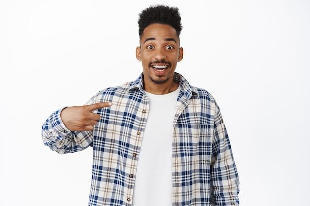 Un afro-américain excité se pointant sur lui-même, levant les sourcils étonnés, étant choisi, l'air plein d'espoir et étonné, debout sur blanc