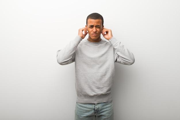 Afro-américain sur fond de mur blanc couvrant les oreilles avec les mains. expression frustrée