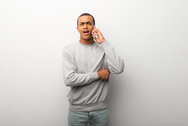Afro-américain sur fond de mur blanc, gardant une conversation avec le téléphone portable avec quelqu'un