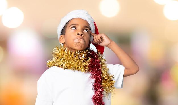 Afro-américain garçon avec chapeau de noël ayant des doutes et avec une expression de visage confuse sur mur flou