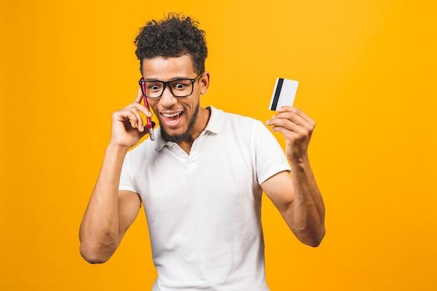 Afro-américain habillé en tenue décontractée, à l'aide de téléphone mobile, montrant une carte de crédit en plastique