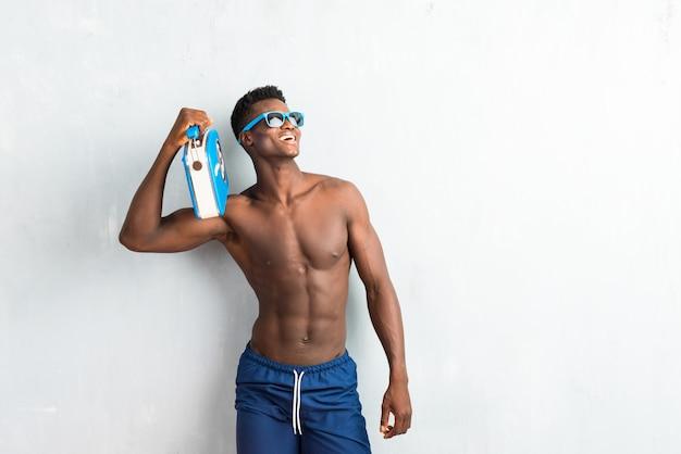 Afro américain homme profitant des vacances d'été tenant une radio vintage et levant