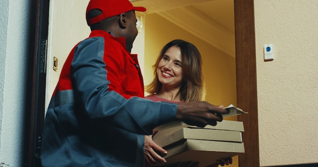 Afro-américain jeune homme en uniforme et casquette livrant une pizza à la femme de race blanche. à l'intérieur.