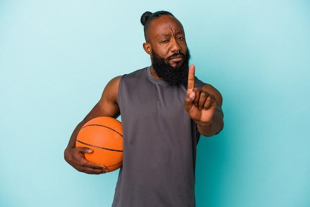 Afro-américain jouant au basket-ball isolé sur fond bleu montrant le numéro un avec le doigt.
