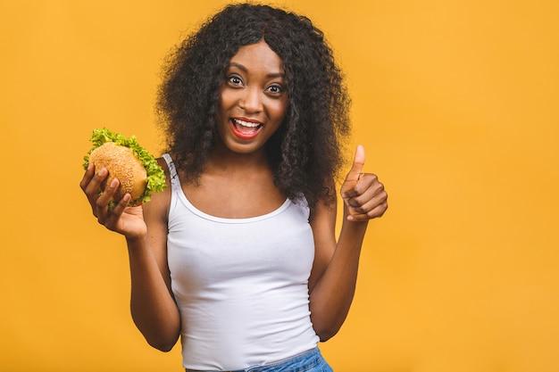 Afro-américain, noir, jeune femme, manger, hamburger