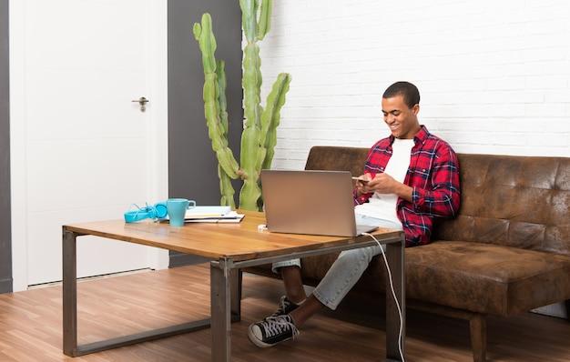 Afro-américain avec ordinateur portable dans le salon en envoyant un email avec le mobile