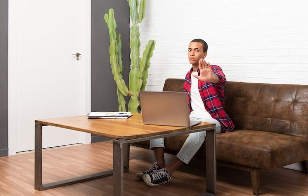 Afro-américain avec ordinateur portable dans le salon faisant un geste d'arrêt niant une situation qui pense mal