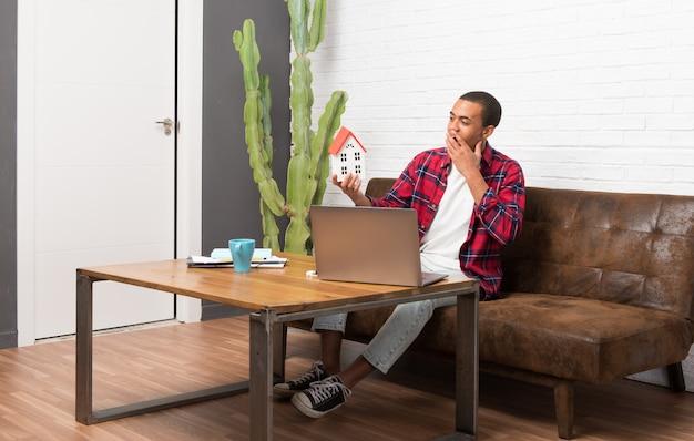 Afro-américain avec ordinateur portable dans le salon, tenant une petite maison