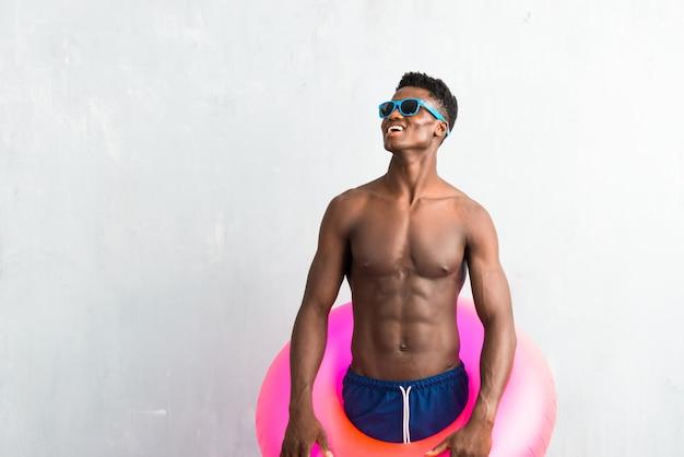 Afro-américain, profitant des vacances d'été avec flotteur et levant