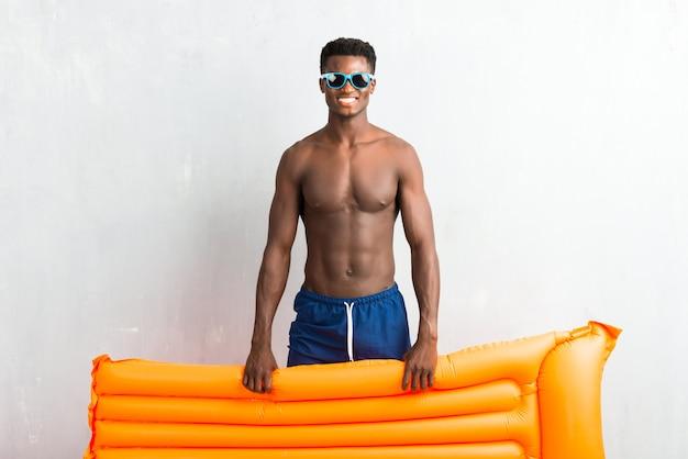 Afro-américain, profitant des vacances d'été avec flotteur