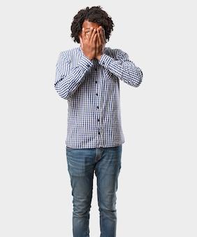 Afro-américain se sent inquiet et effrayé, regardant et couvrant le visage, concept de peur et d'anxiété