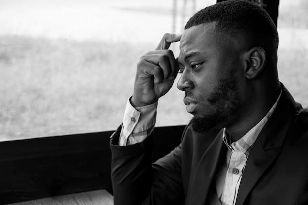 Afro-américain songeur fatigué jeune homme d'affaires est assis dans un café. portrait de jeune homme noir regarde la fenêtre tourne la tête et regarde la caméra. le jeune barbu porte une chemise et une veste de costume.
