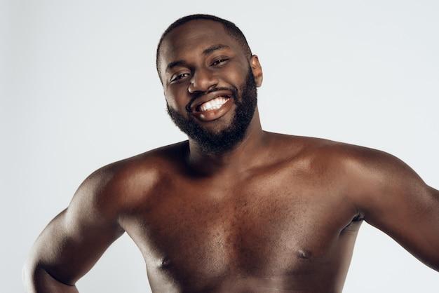 Afro-américain souriant homme nu pose