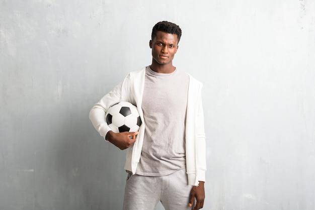 Afro-américain sportif tenant un ballon de foot