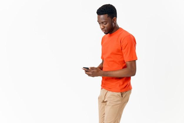 Afro-américain en t-shirt avec un téléphone portable à la main sur fond clair