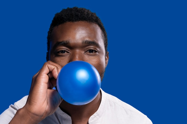Afro-américain tenant un ballon bleu