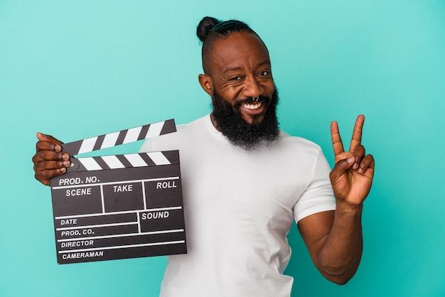 Afro-américain tenant un clap isolé sur un mur bleu montrant le numéro deux avec les doigts.