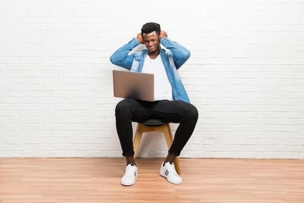 Afro-américain travaillant avec son ordinateur portable couvrant les deux oreilles avec les mains