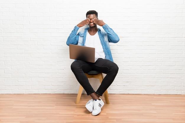 Afro-américain travaillant avec son ordinateur portable couvrant les yeux par les mains