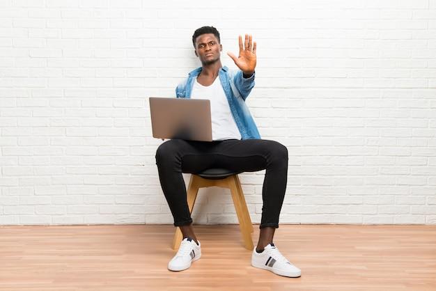 Afro-américain travaillant avec son ordinateur portable, faisant un geste d'arrêt avec sa main