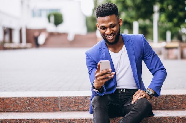 Afro-américain en veste bleue à l'aide de téléphone