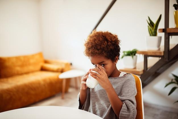 Afro-américaine boit du lait à la maison.