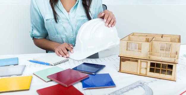 Afro-américaine dame sur une chaise tenant un casque de sécurité près du plan et modèle de maison sur la table