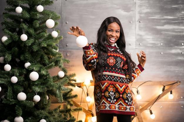 Afro américaine femme suspendue des jouets sur un arbre de noël