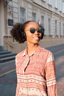 Une afro-américaine noire se promène en ville le soir et écoute de la musique au casque. fille à lunettes de soleil en été sourit et regardant le coucher du soleil.