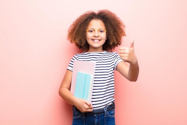 Afro-américaine petite fille contre un mur plat tenant un livre