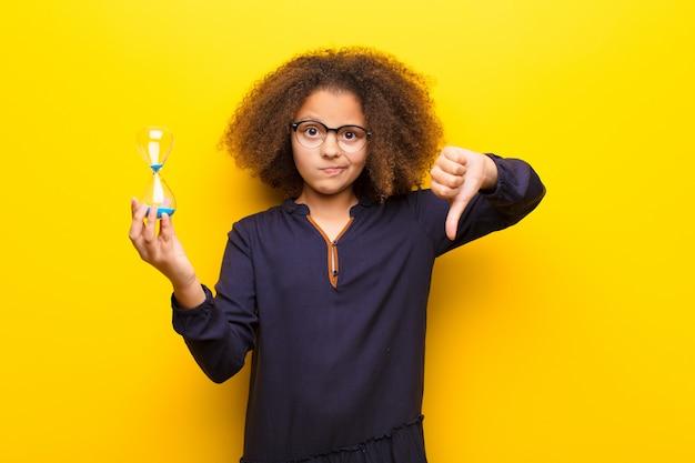 Afro-américaine, petite fille, contre, mur plat, tenue, a, horloge sable, minuterie