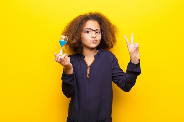 Afro-américaine petite fille sur un mur plat tenant une minuterie d'horloge de sable