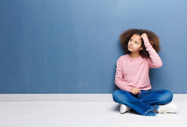 Afro-américaine petite fille se sentant perplexe et confus, se grattant la tête et regardant sur le côté, assis sur le sol